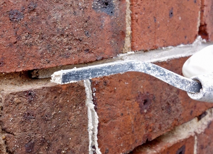 Close up of red brick wall with section of mortar being replaced with a hand tool