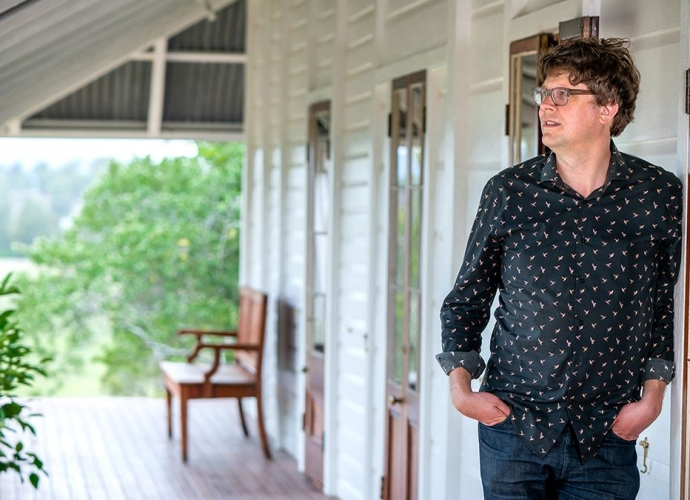 Stuart Harrison standing on the verandah of a heritage house.