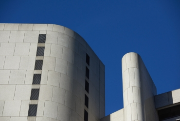 The top details of a large concrete building, clear sky
