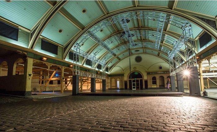 A large empty room with cobble stone floor, a colourful painted wooden arched roof.